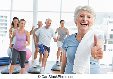 Senior woman gesturing thumbs up with people exercising -...