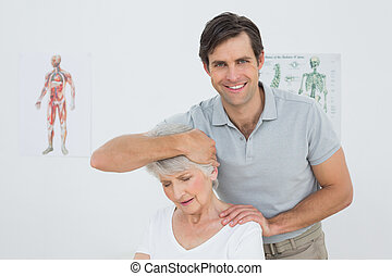 Senior woman getting the neck adjustment done in the medical...