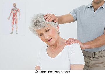 Senior woman getting the neck adjustment done - Senior woman...