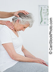 Senior woman getting the neck adjustment done - Side view of...