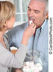 senior woman giving a bonbon to her husband