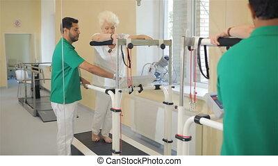 Senior woman goes on rehabilition treadmill
