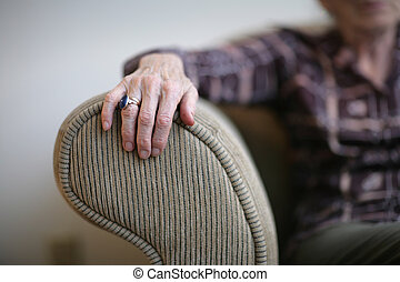 Senior woman hand on an armrest. Shallow DOF.