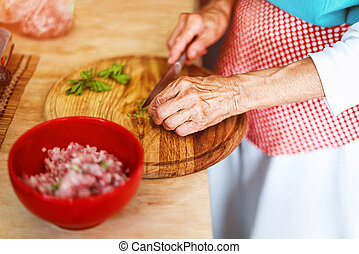Senior woman hands chopping vegetables on a wooden board in the kitchen.