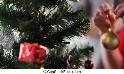 senior woman hands decorating christmas tree - holidays ,...