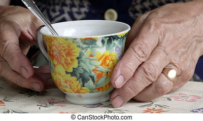 Senior woman hands holding cup of some drink