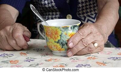 Senior woman hands with a cup of tea closeup