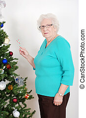 Senior woman hanging candy cane