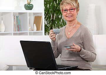 Senior woman having a coffee in front of her laptop computer