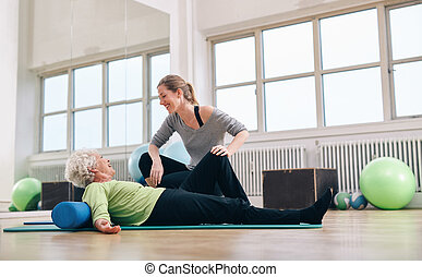 Senior woman having a friendly chat with her personal trainer
