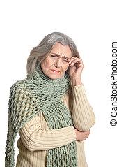 senior woman having a headache, posing against white