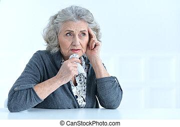 senior woman having a headache posing against white