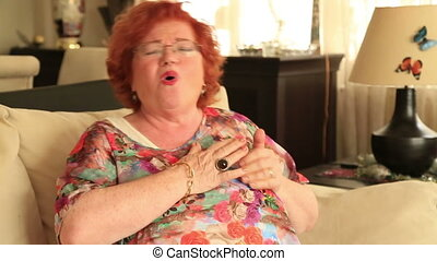 Senior woman having a heart attack - Mature woman sitting on...