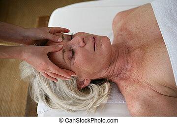senior woman having a massage in a spa center