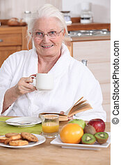 Senior woman having a relaxed breakfast