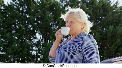 Senior woman having coffee on terrace 4k - Thoughtful senior...