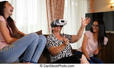 Senior woman having fun with virtual reality glasses and her granddaughters