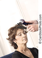 Senior woman having haircut