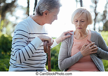 Senior woman having pain in her chest outdoors