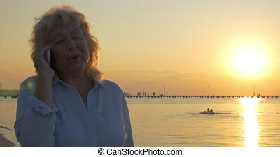 Senior woman having phone talk on beach at sunset