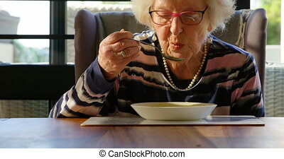 Senior woman having soup on dining table at home 4k