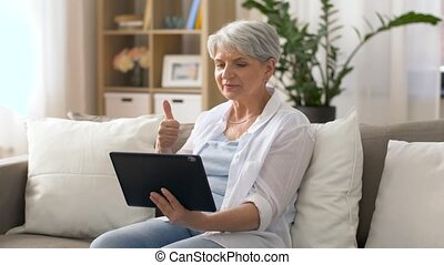 senior woman having video chat on tablet pc - technology,...