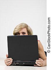 Senior woman hiding behind laptop