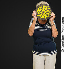 Senior Woman Hiding Face With Dartboard