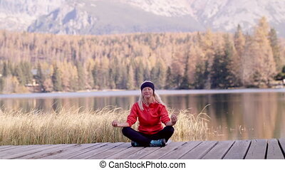 Front view of senior woman hiker sitting outdoors by lake in nature, doing yoga exercise.