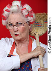 senior woman holding a broom