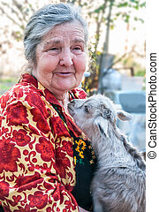 Senior woman holding a goatling on a background of his home