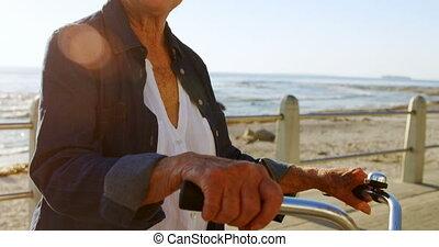 Senior woman holding bicycle at promenade 4k - Senior woman...
