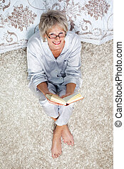 Senior Woman Holding Book While Sitting On Rug In Bedroom