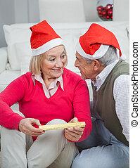Senior Woman Holding Christmas Gift Looking At Man