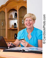 senior woman holding credit card