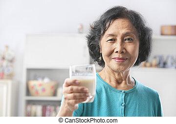 Senior woman holding glass of milk