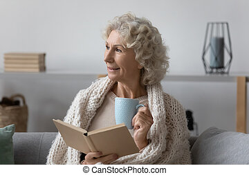 Senior woman holding paper book and hot tea.