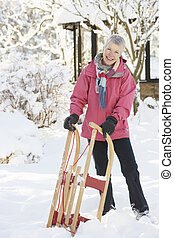 Senior Woman Holding Sledge In Snowy Landscape