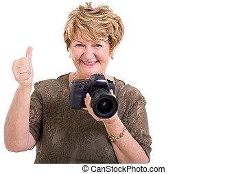 senior woman holding SLR camera and giving thumb up