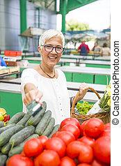 Senior woman holds credit card on market