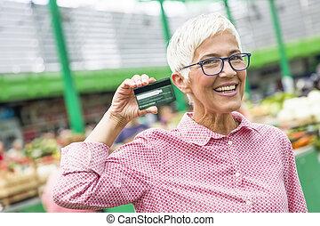 Senior woman holds credit card