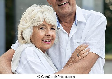 Senior woman hugging her husband