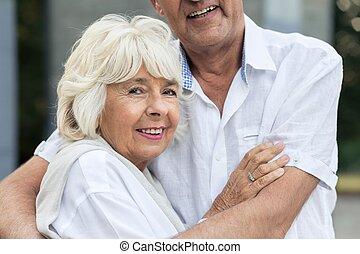 Senior woman hugging her husband