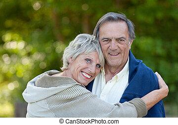 Senior woman hugging her partner outdoors