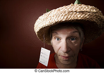 Senior woman in a cheap straw hat
