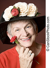 Senior woman in a hat with flowers