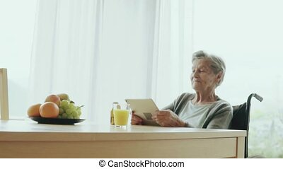 Senior woman in a wheelchair with tablet at home. An elderly...