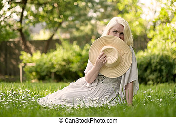 Senior woman in dress sitting on grass at the park