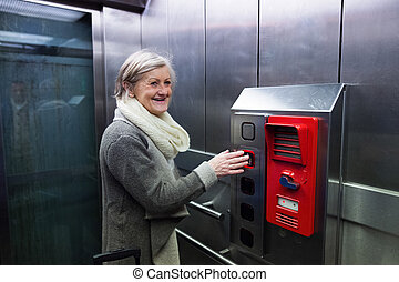 Senior woman in elevator on train station travelling.