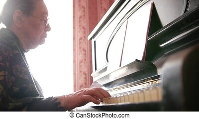 Senior woman in eyeglasses is playing the piano, close up